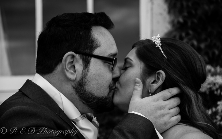 black and white wedding photography bride and groom kiss