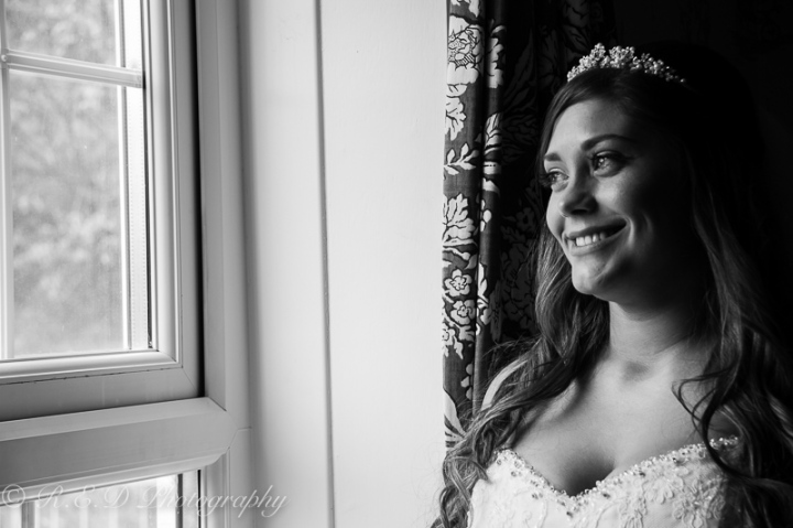 black and white wedding photography bride looking out at window